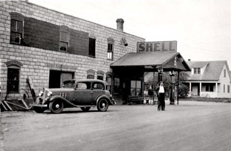Al Bailey standing in front of the Shell station, Tenstrike Minnesota, 1930