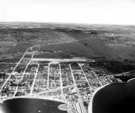 Aerial view of Grand Marais on the north shore of Lake Superior, white line is the Gunflint Trail, 1955