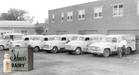 A row of six Schwan's trucks with drivers standing next to each